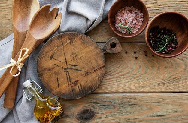 Старая винтажная кухонная утварь. деревянные ложки, разделочная доска, салфетка и специи над старым деревянным столом. вид сверху