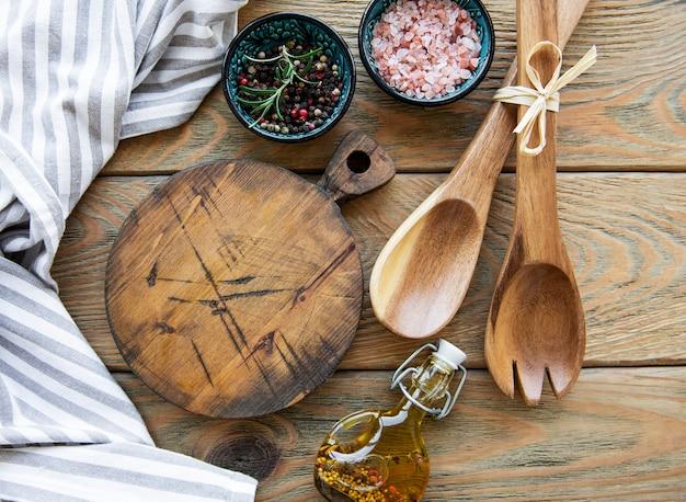 古いヴィンテージの台所用品。古い木製のテーブルの上に木のスプーン、まな板、ナプキン、スパイス。上面図
