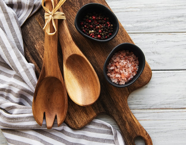 古いヴィンテージの台所用品。木製のスプーン、まな板、ナプキン、白い木製のテーブルの上のスパイス。上面図
