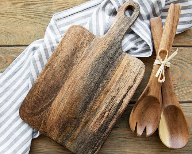 古いヴィンテージの台所用品。白い木製のテーブルの上に木のスプーン、まな板、ナプキン、スパイス。上面図