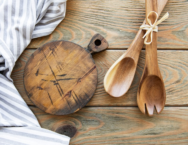 Old vintage kitchen utensils. wooden spoons,  cutting board, napkin. over old  wooden table. top view