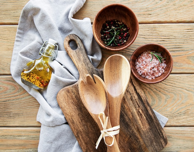 Old vintage kitchen utensils. wooden spoons,  cutting board, napkin and spices over old wooden table. top view