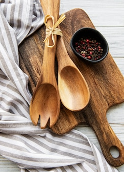 Old vintage kitchen utensils. wooden spoons,  cutting board, napkin and spices over white wooden table. top view