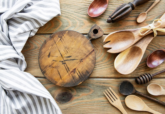 Old vintage kitchen utensils. wooden spoons,  cutting board, napkin. over white wooden table. top view