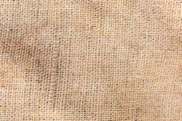 古いヴィンテージのリネン生地のテキスタイル。黄麻布の素朴なタンブルテクスチャの背景。