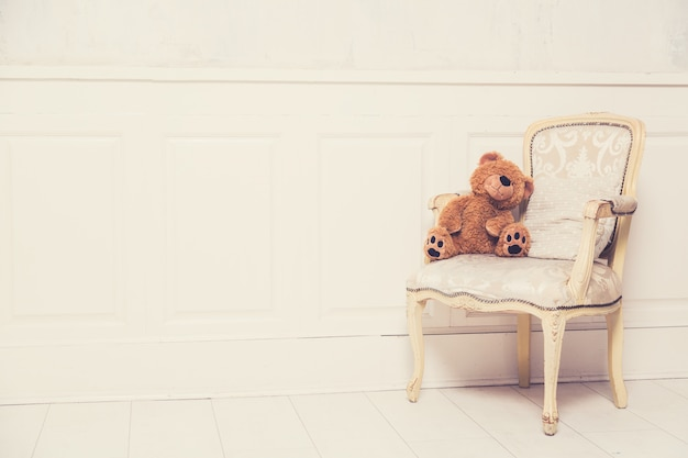 Old vintage luxury armchair with a teddy bear. vintage toned