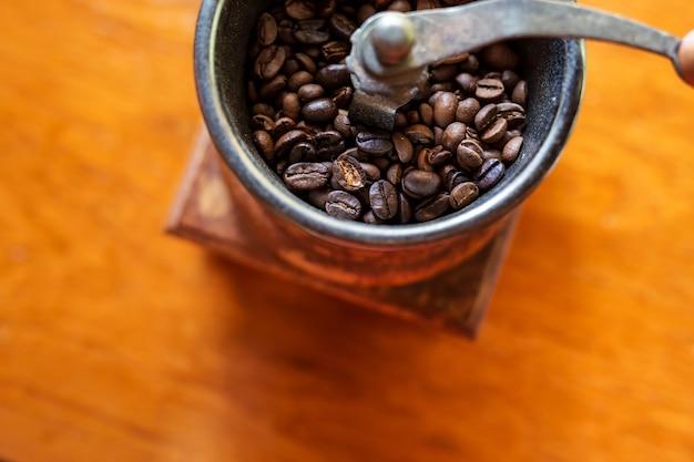 コーヒーショップで焙煎したコーヒー豆と古いヴィンテージ手動グラインダー