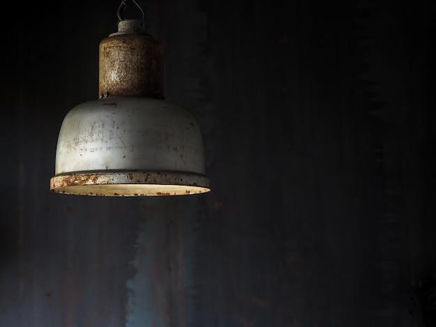 Old vintage metal ceiling lamp hanging in dark room