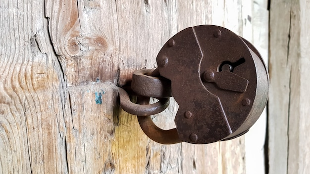 Old vintage metal padlock on a closed wooden door of an old farmhouse.
