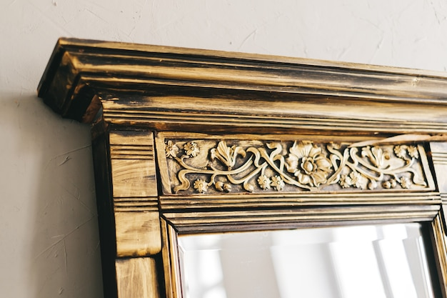 골드 컬러 나무 장식 프레임 오래 된 빈티지 거울. 확대.