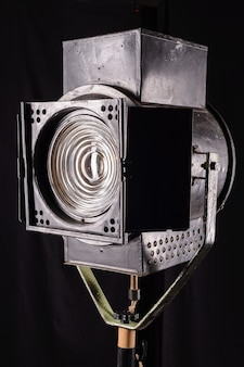 Old vintage movie spotlight on black surface.