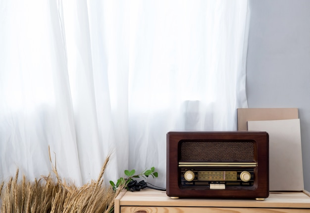Old vintage radio with shelf on wooden cabinet