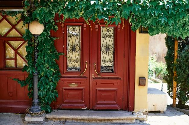 トビリシ市の屋外の古いヴィンテージの赤い木製のドアとアンティークの街灯