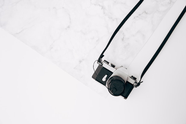 An old vintage retro camera on marble textured and white background