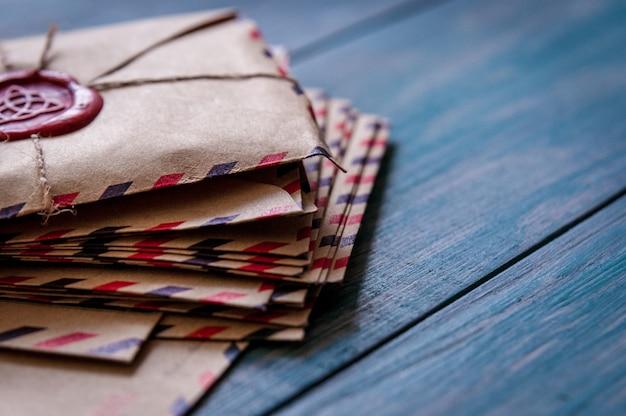 古い青い木製のテーブルにワックススタンプが付いた古いビンテージレトロな封筒