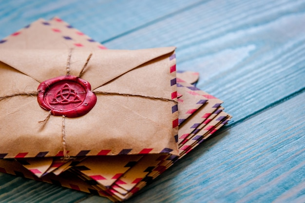 Old vintage retro envelopes with a wax stamp on old blue wooden table
