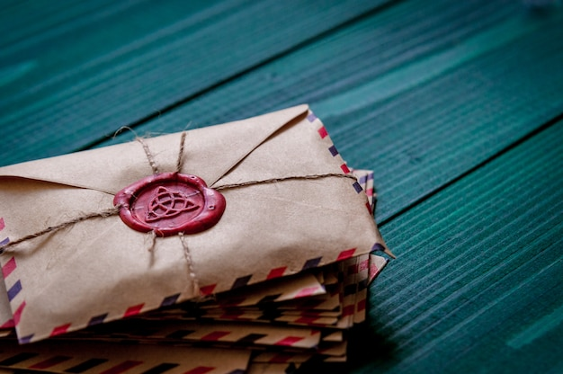 Old vintage retro envelopes with a wax stamp on old dark green wooden table