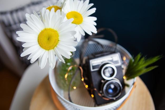 木の板にデイジーの花の花束を持つ古いビンテージ素朴なカメラ。