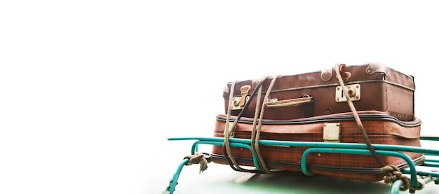 오래된 빈티지 여행가방은 흰색 배경에 글씨를 쓰기 위해 분리된 녹색 자동차 지붕에 밧줄로 묶여 있습니다. 가족 휴가를 위한 소풍을 위한 여행이나 여행의 개념. 배너 저작권 공간