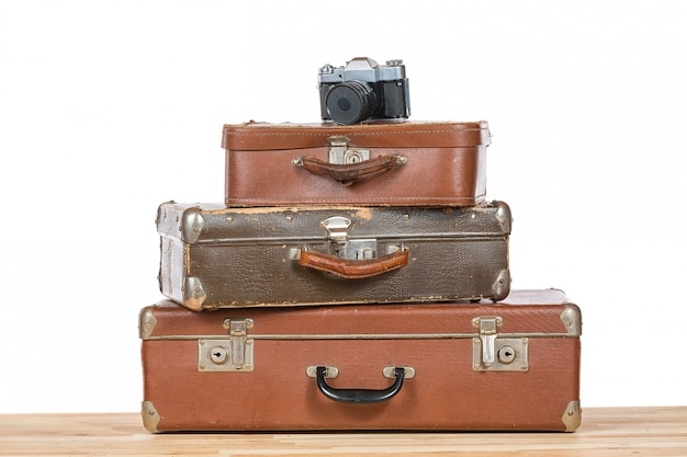 Old vintage suitcases with retro photo camera on light wooden table isolated