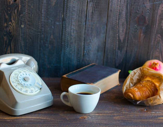 Old vintage telephone coffee book on a wooden background