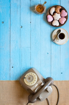 Old vintage telephone, with biscotti, coffee, donuts on a wooden background