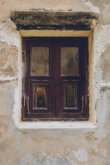 古いヴィンテージの伝統的な木製の窓とセメントの壁