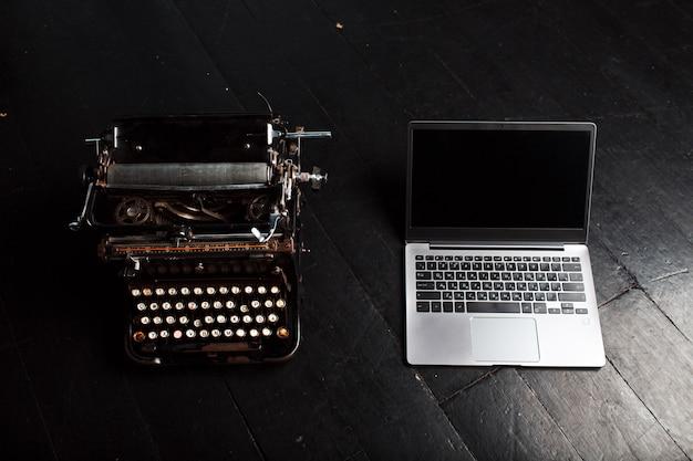 Старая винтажная машинка и современный ноутбук.
