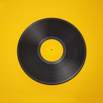 Old vintage vinyl record isolated on yellow background