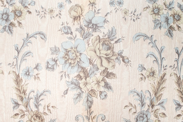 Old vintage wallpaper on the wall with a pattern of flowers