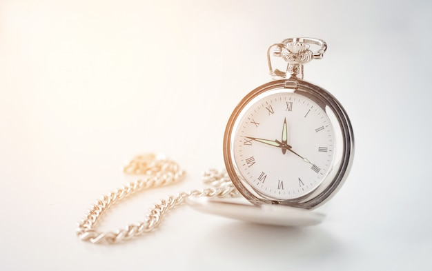 Old vintage watch on a chain on a white background