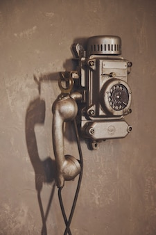 Old vintage wired telephone for communication hangs on textured gray wall. antique phone from past for background. history of telephone in world. concept of communications and telegraph. copy space
