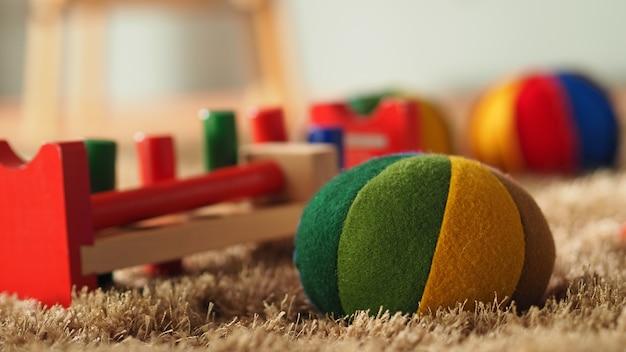 Старые старинные деревянные игрушки для малышей или детей на светло-коричневом ковре с мячом для автобуса. Premium Фотографии