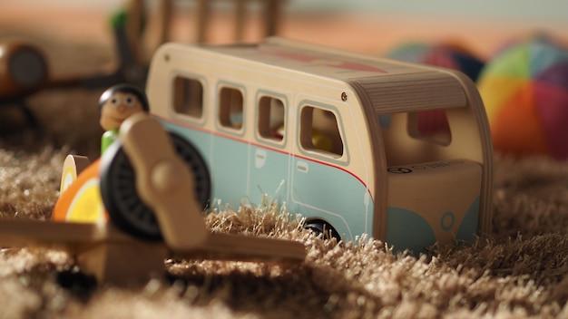 Старые старинные деревянные игрушки для малышей или детей на светло-коричневом ковре с мячом для автобуса.