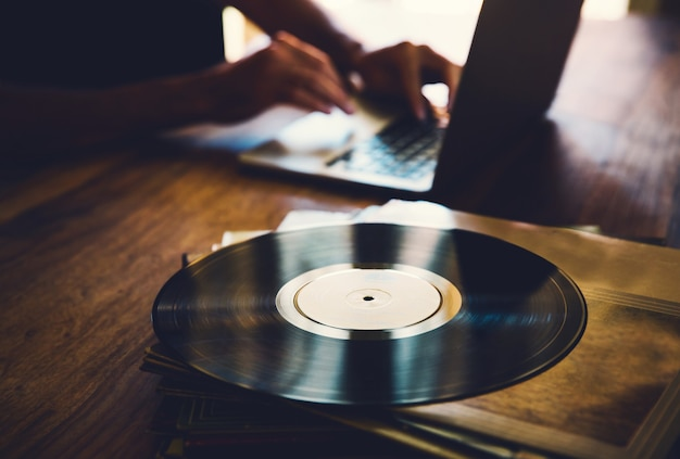 Old vinyl record and a collection of albums on wooden table