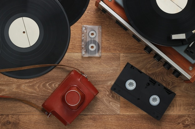 Old vinyl record player, video cassettes, audio cassette, old-fashioned film camera on the floor. retro media 80s. top view
