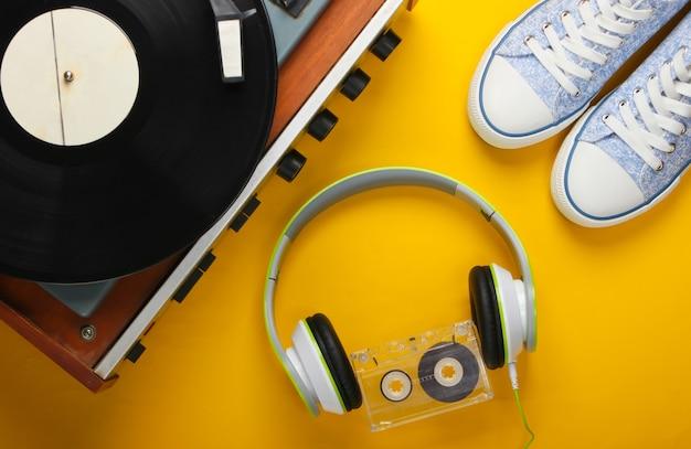 黄色の表面にステレオヘッドフォン、オーディオカセット、スニーカーを備えた古いビニールレコードプレーヤー