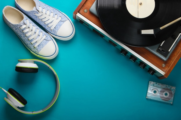 Old vinyl record player with stereo headphones, audio cassette and sneakers on blue surface