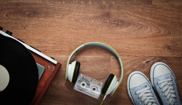 Old vinyl record player with stereo headphones, audio cassette and sneakers on a wooden floor