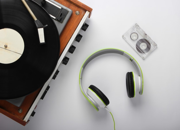 Old vinyl record player with stereo headphones and audio cassette on white surface