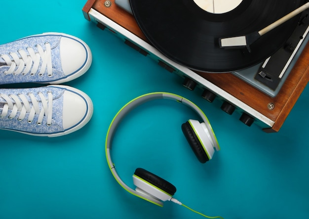 Old vinyl record player with stereo headphones and sneakers on blue surface