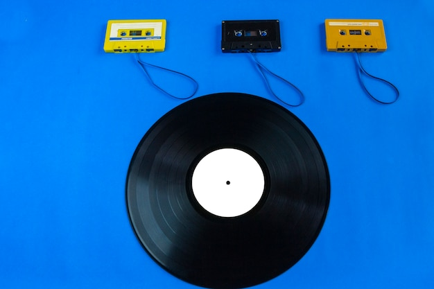 Old vinyl records and tape cassette on blue background