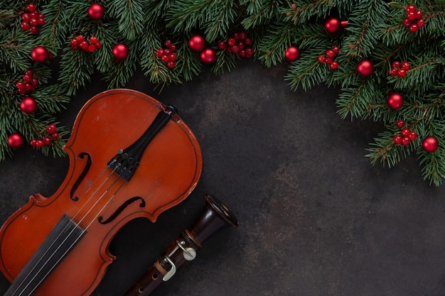 Old violin and flute with fir-tree branches with christmas decor.   top view, close-up