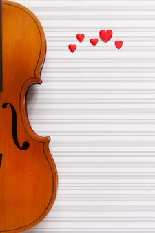 Old violin and red heart figurines. top view, close up,on white music paper background