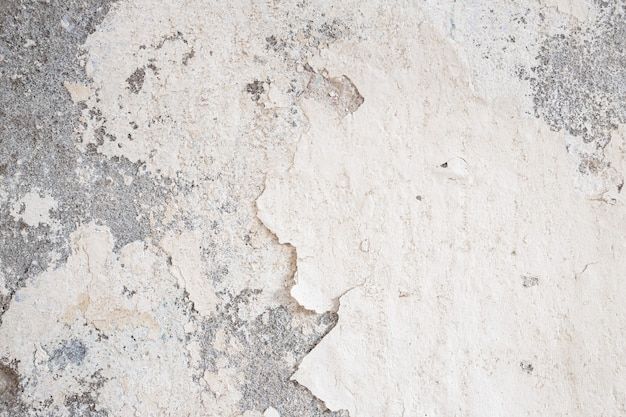 Old wall damaged with blown plaster and paint clog, peeling paint damage, water damage on building wall. grunge abstract background