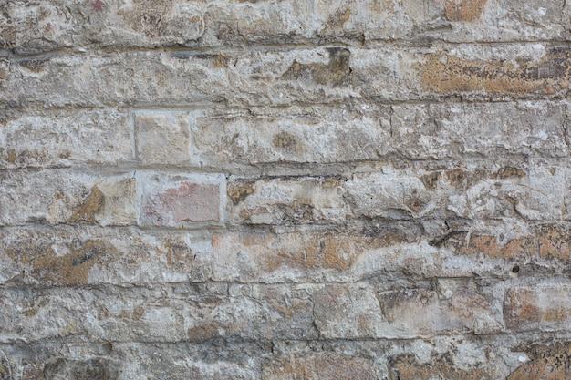 Старая стена сделанная из больших камней и сломанных кирпичей. старинные шероховатые блоки поверхности фона