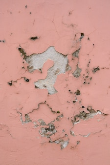 Old wall texture flaking pink paint background