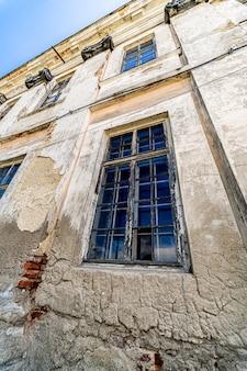 필 링 페인트와 함께 오래 된 벽입니다. 긁힌 스테인드 석고와 닫힌 창문. 아래에서 볼 수 있습니다.