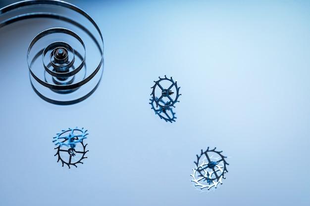 거울 표면의 오래된 시계 부품, 스프링 및 기어