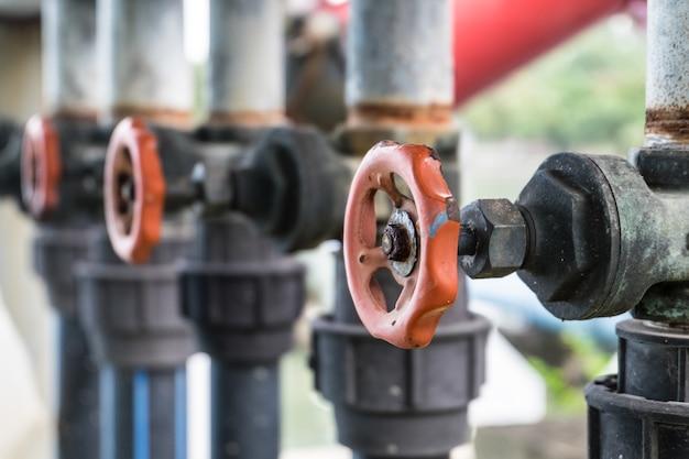 Старый водяной клапан и труба соединяются с насосом в озеро в общественном парке.
